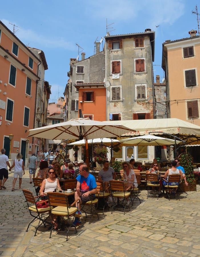Matställear på tabeller i en restaurang i den gamla staden av Rovinj Kroatien arkivfoto