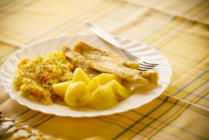 Matställemålfisk med sallad och potatisar royaltyfria bilder