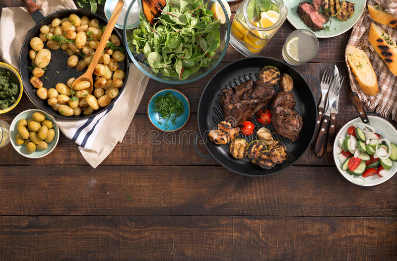 Matställetabell med grillad biff, grönsaker, potatisar, sallad, sn arkivfoto