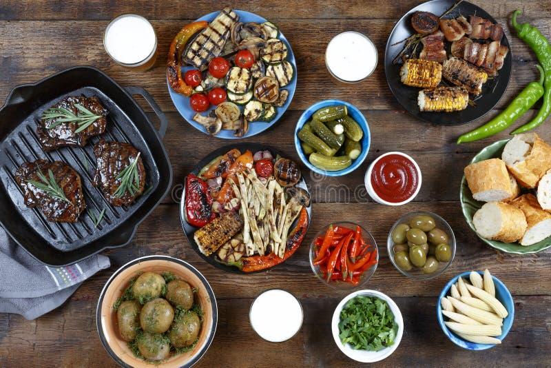 Matställetabell med köttgallret, bbq-grönsaker, sallader, såser, mellanmål och öl, bästa sikt royaltyfri bild
