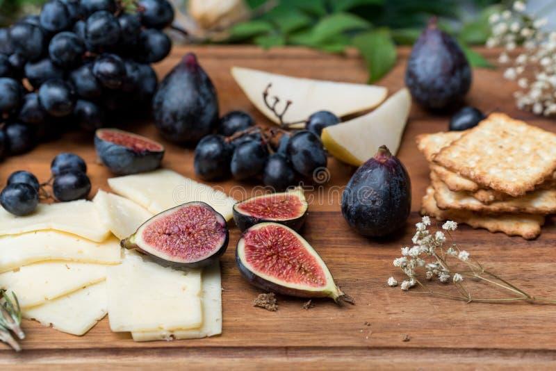 Matstilleben med ost, druvor och fikonträd arkivfoton