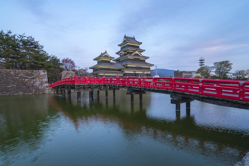 Matsumoto Castle at twilight with the red bridge in Nagano, Japan royalty free stock photos