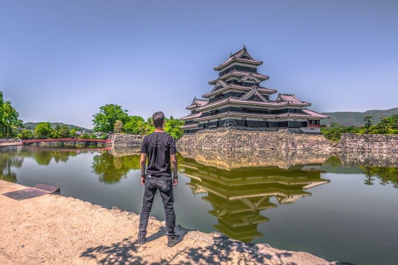 Matsumoto - 25 de maio de 2019: O castelo de Matsumoto e a ponte vermelha que o leva, Japão fotografia de stock