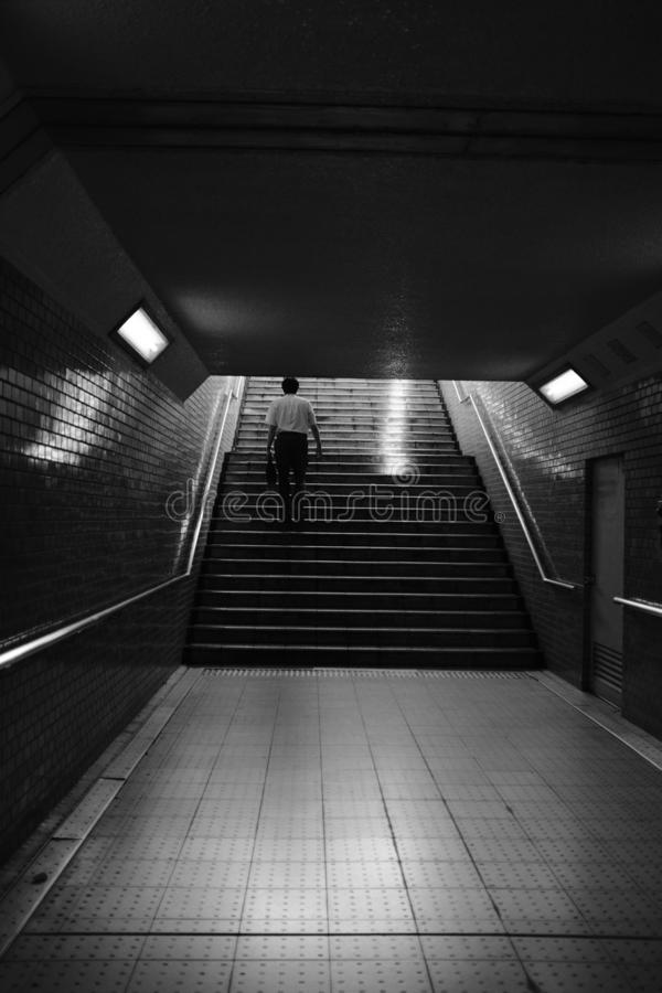 Grayscale vertical shot of a person climbing underground stairs with steel handrails on brick walls royalty free stock photos
