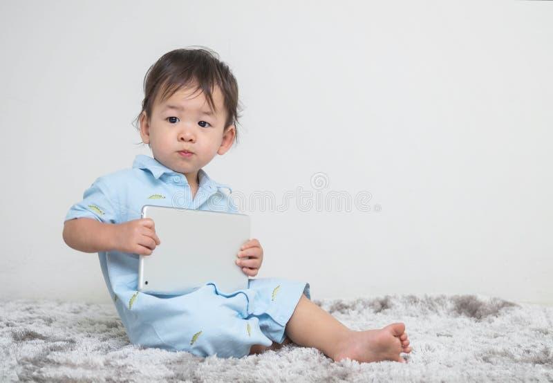Mattar cementerar gulligt asiatiskt ungesammanträde för closeupen med minnestavlan på hans hand hemma på grå färger och väggen te royaltyfri bild