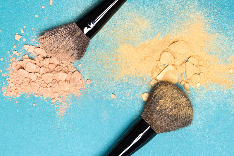Matte compact powder and shimmer powder with makeup brushes. Close-up of crushed mineral matte compact powder and shimmer powder golden color with makeup brushes royalty free stock photography