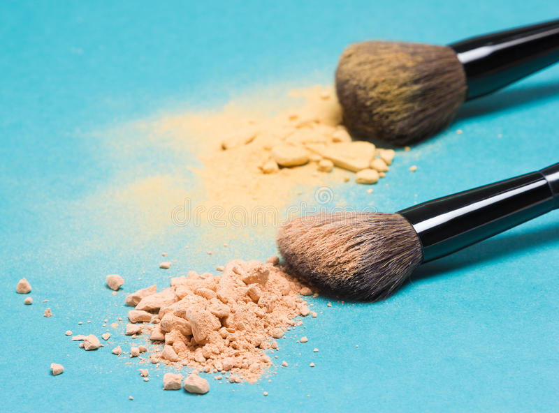 Matte compact powder and shimmer powder with makeup brushes. Close-up of crushed mineral matte compact powder and shimmer powder golden color with makeup brushes royalty free stock image