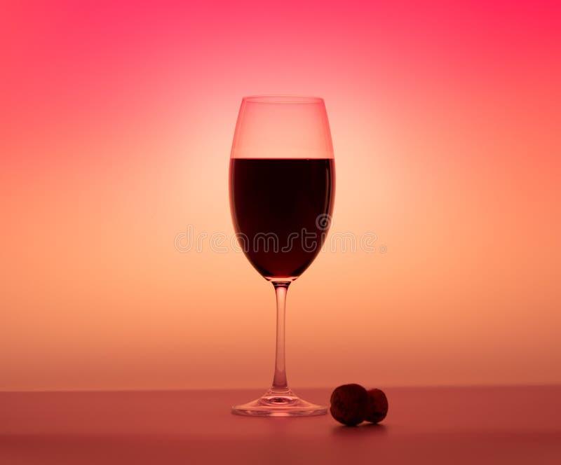 Matte wineglass half red wine orange background cork on table stock image