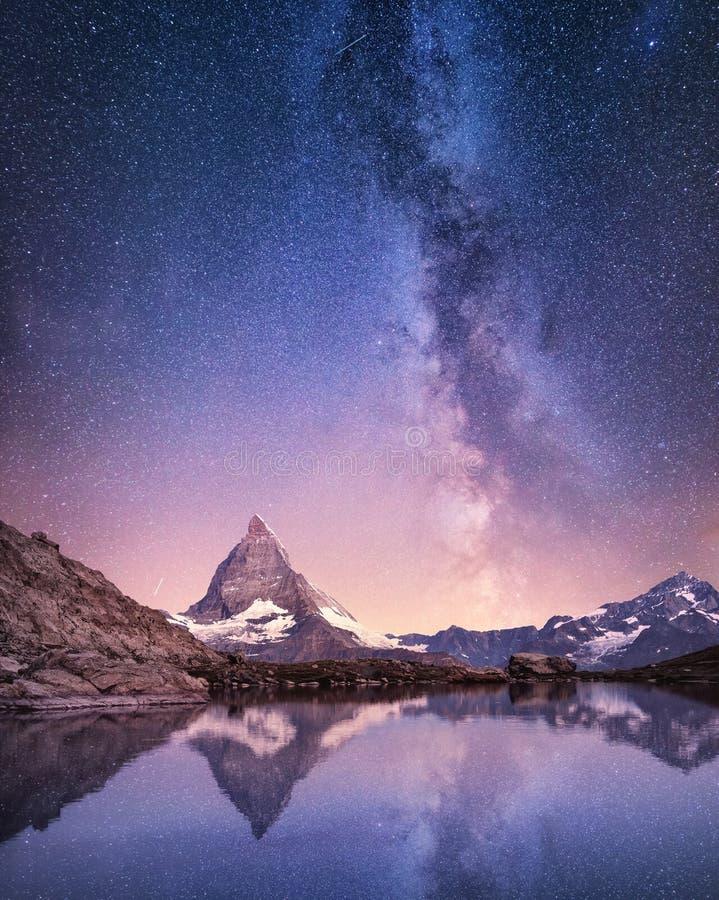 Matterhorn e a reflexão na água surgem na noite Via Látea acima de Matterhorn, Suíça fotografia de stock