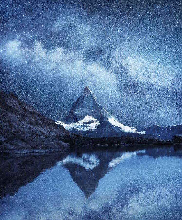 Matterhorn e a reflexão na água surgem na noite Via Látea acima de Matterhorn, Suíça imagem de stock