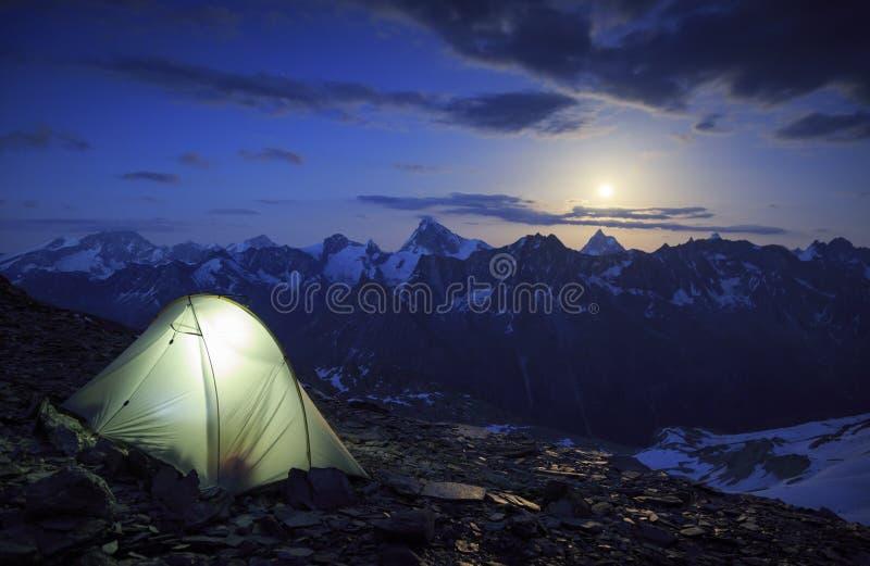 Matterhorn moonrise. Campsite and the moon rising above the Matterhorn in Wallis, Switzerland. Outdoor and adventure concept stock photos