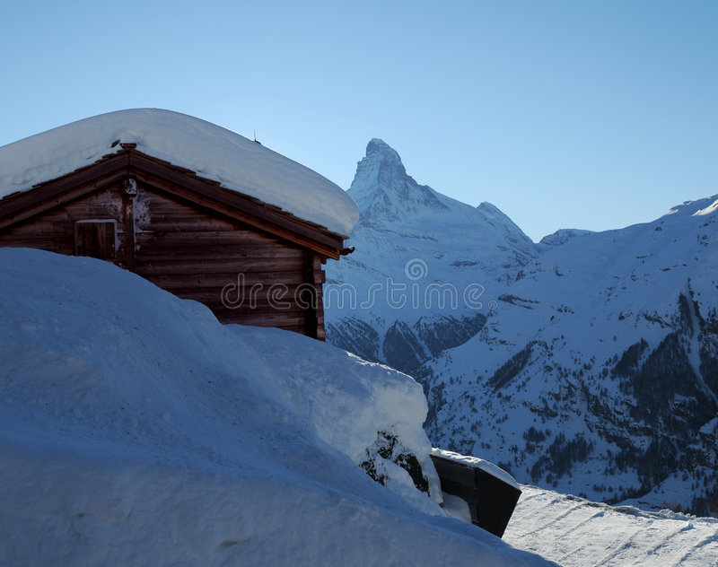 Matterhorn mountain. Log cabin in snowy landscape with Matterhorn mountain in background, Pennine Alps, Switzerland and Italy royalty free stock images