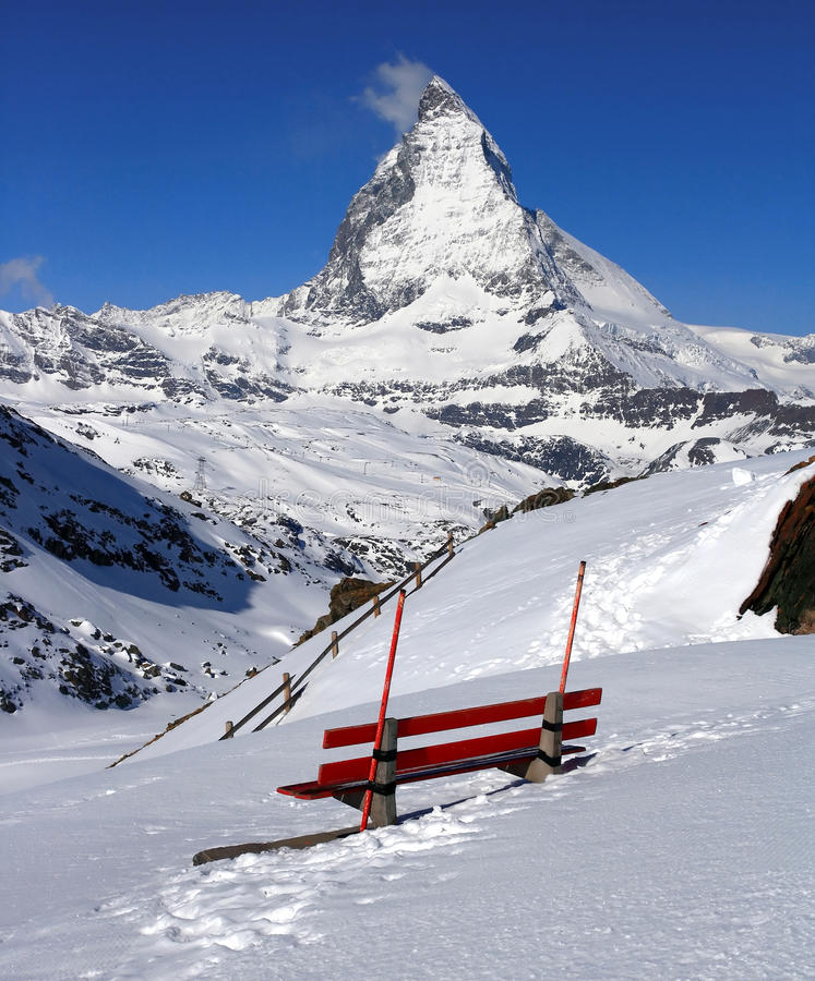 Matterhorn Peak with Red Chair. Red chair and Matterhorn, logo of Toblerone chocolate, located in Switzerland stock image