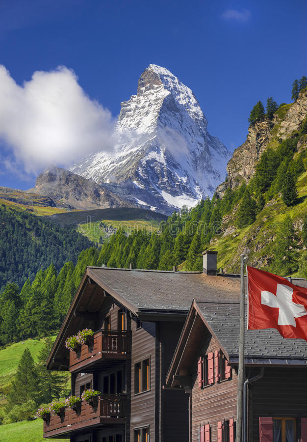 Matterhorn and Swiss flag. View of Matterhorn from Zermatt with Swiss flag near a wooden traditional house. Switzerland. (landscape orientation stock photo