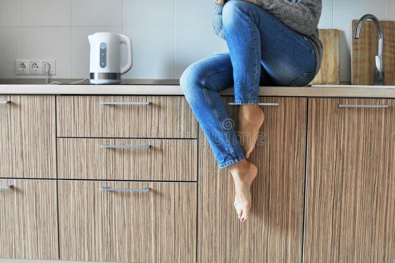 Mattina accogliente: caffè bevente della bella ragazza su una sedia nella cucina nello stile scandinavo immagini stock
