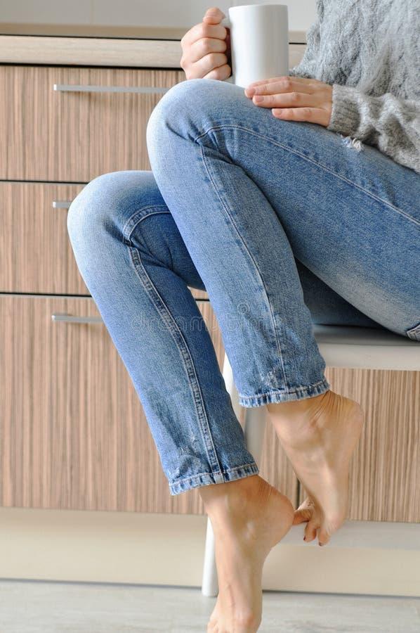 Mattina accogliente: caffè bevente della bella ragazza su una sedia nella cucina nello stile scandinavo immagini stock libere da diritti