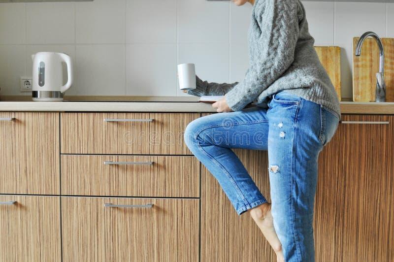 Mattina accogliente: caffè di lavoro e bevente della bella ragazza su una sedia nella cucina nello stile scandinavo fotografia stock libera da diritti
