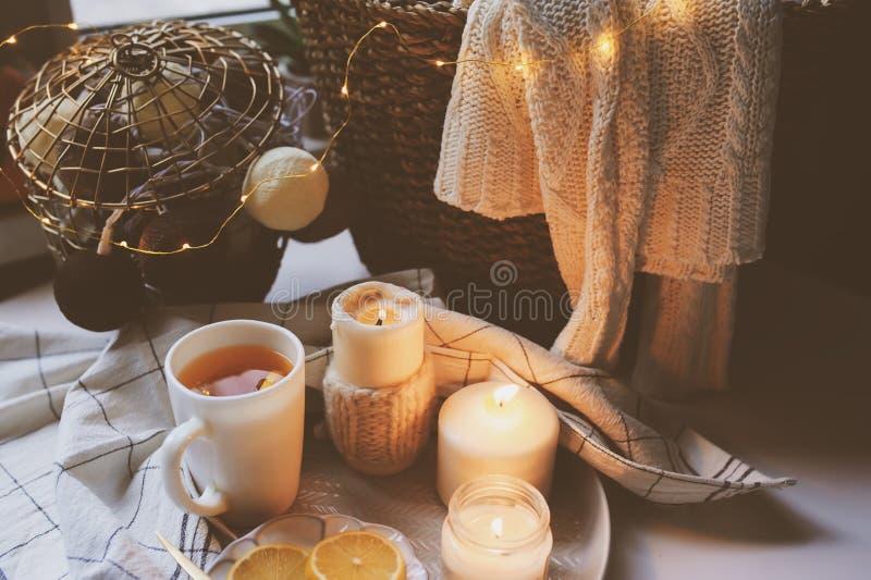 Mattina accogliente di inverno a casa Il tè caldo con il limone, candele, ha tricottato la merce nel carrello dei maglioni ed i d immagini stock