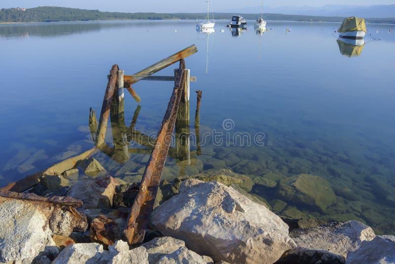 Mattina alla baia; vecchio pilastro arrugginito e barche ancorate immagini stock