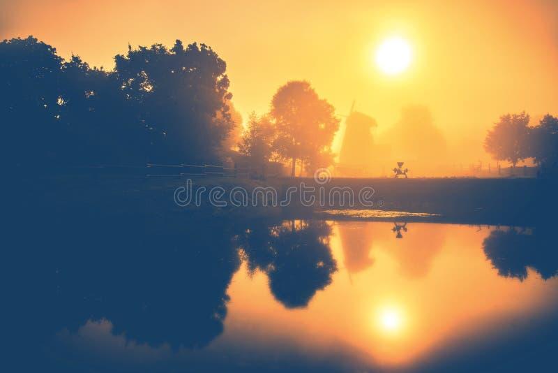 Mattina arancio di alba nebbiosa vicino ad acqua ed al mulino a vento immagine stock libera da diritti