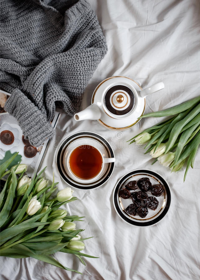 Mattina con i tulipani di bianco e del tè su un letto accogliente immagini stock libere da diritti