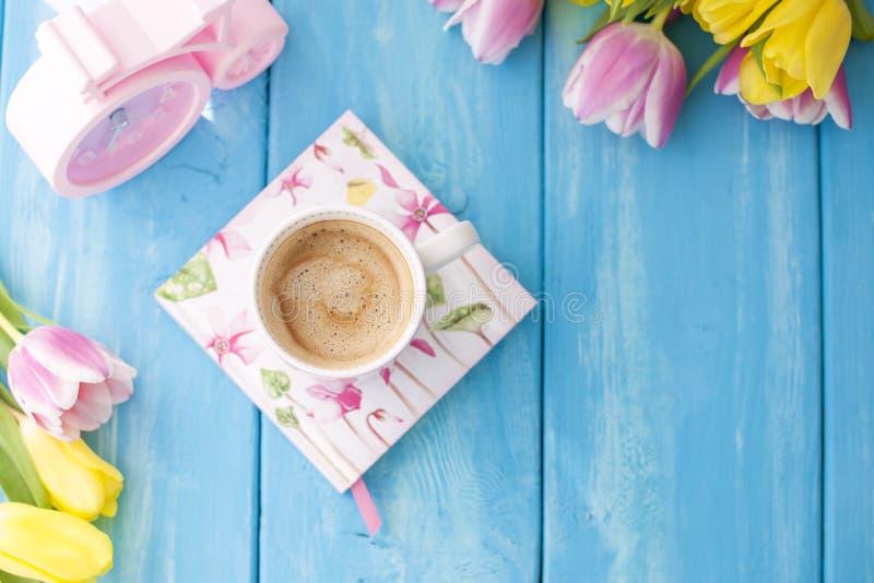Mattina della primavera, caffè fragrante e tulipani di colore giallo e rosa Copie di Donuttsy Fondo di legno blu, posto per testo immagini stock libere da diritti