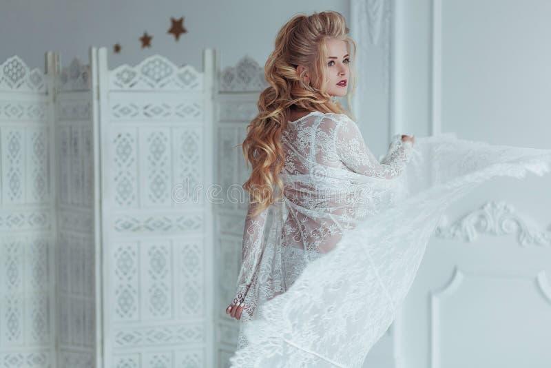 Mattina della sposa Bella giovane donna in veste da camera bianco che gioca con il velo il vestito si sviluppa nel vento Ragazza  immagine stock libera da diritti