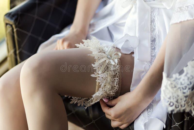 Mattina della sposa, la sposa indossa una giarrettiera di nozze sulla gamba, a immagini stock libere da diritti