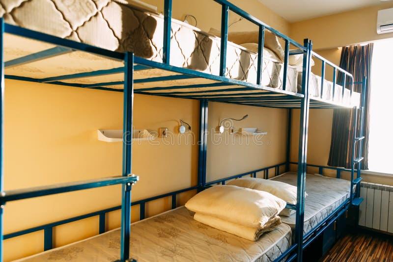 Mattina dentro la camera da letto dell'ostello con i letti bianchi puliti per gli studenti fotografie stock