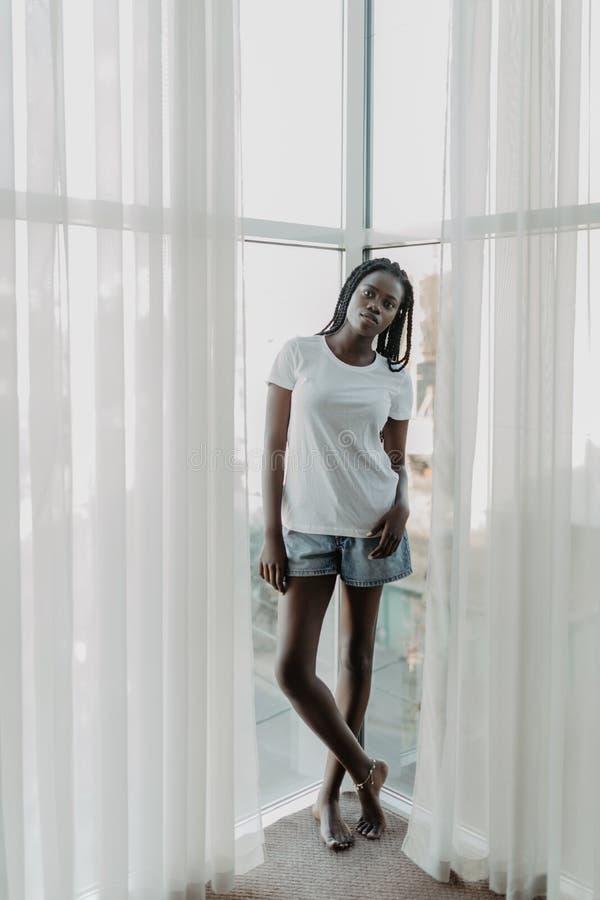 Mattina di bella condizione afroamericana della donna vicino alla finestra in tende fotografia stock