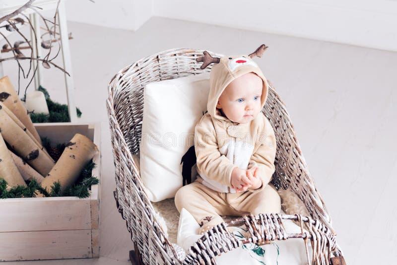 Mattina di natale Bambina nei cervi della tuta che si siedono in un toboggan fotografia stock