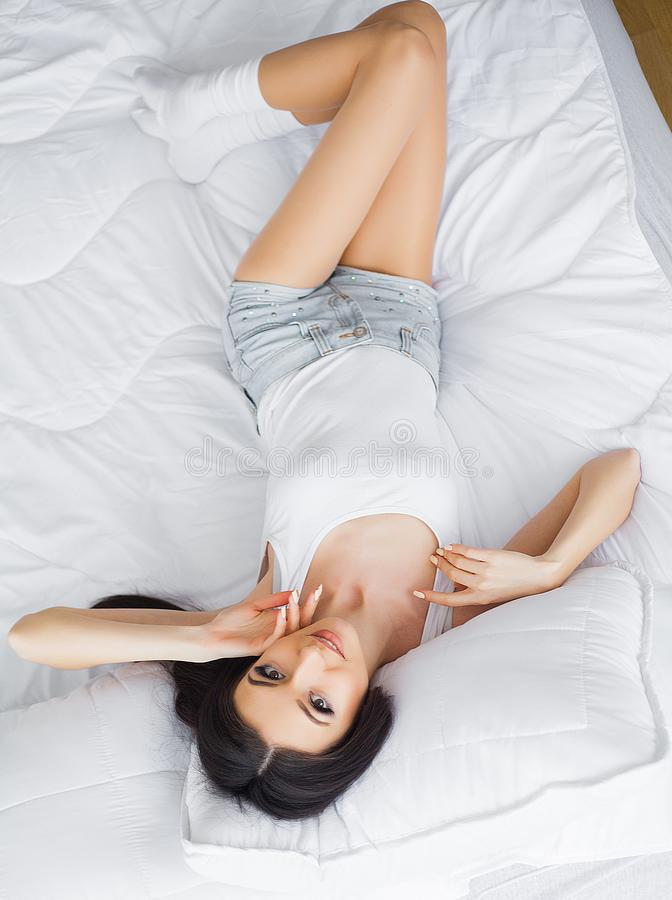 Mattina felice Ritratto di un sorridere donna castana abbastanza giovane che si rilassa nel letto bianco fotografia stock