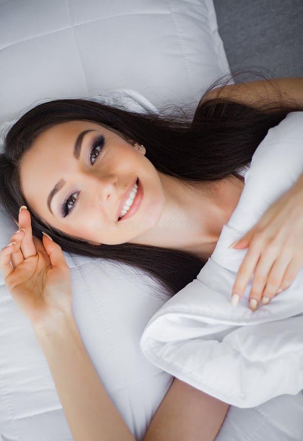 Mattina felice Ritratto di un sorridere donna castana abbastanza giovane che si rilassa nel letto bianco fotografia stock libera da diritti