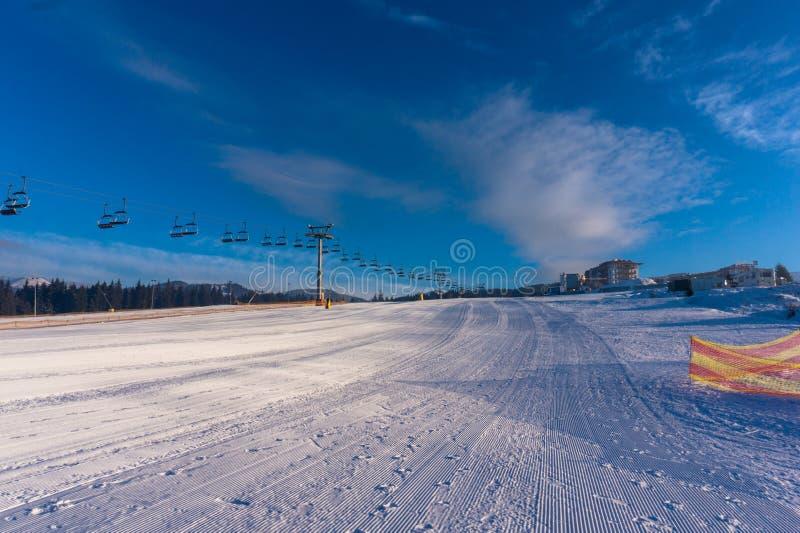Mattina gelida di inverno Pista di sci alpino e ascensore di sci immagini stock libere da diritti