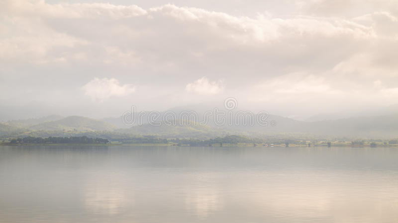 Mattina nebbiosa del lago e della catena montuosa immagini stock