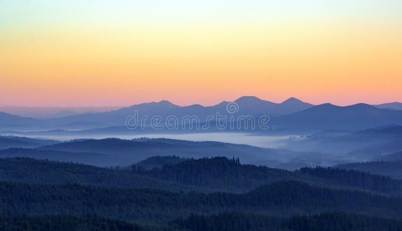Mattina nebbiosa nelle montagne con le siluette delle colline Alba di serenità con luce solare e gli strati morbidi di foschia fotografia stock