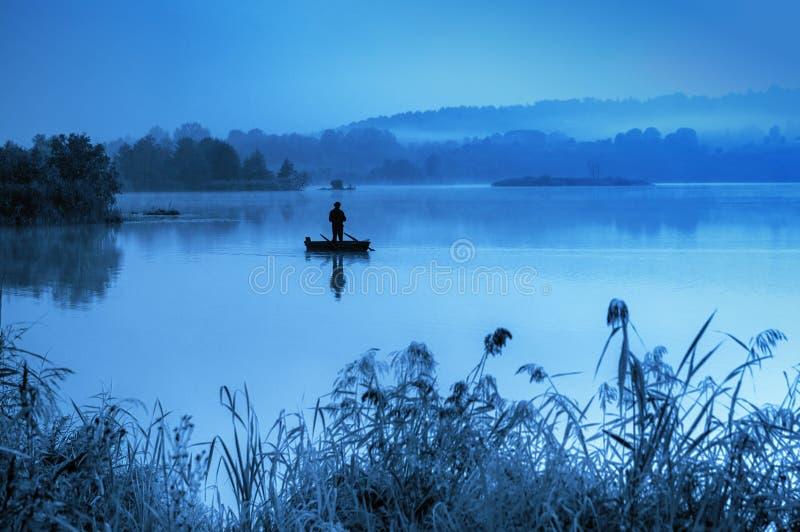 Mattina nebbiosa, pesca dell'uomo nel lago fotografie stock