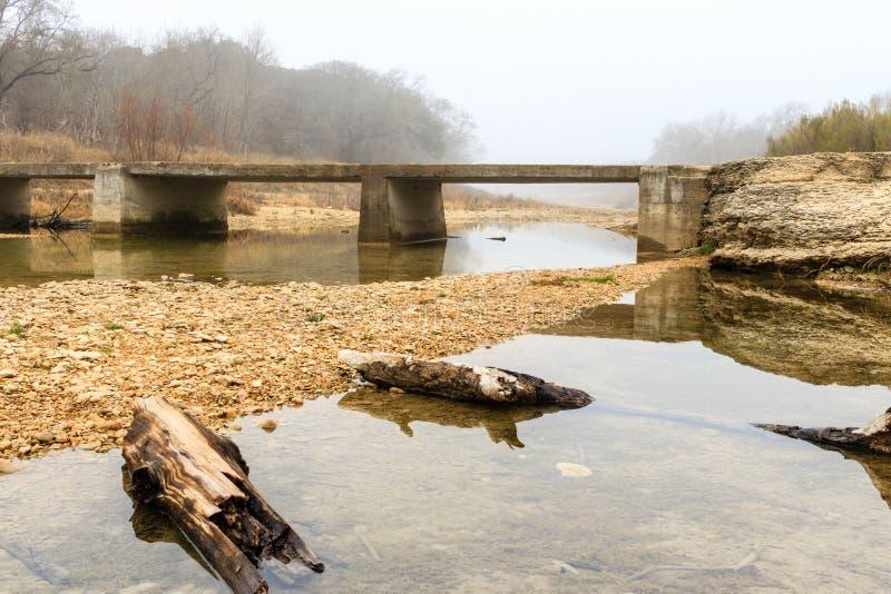 Mattina nebbiosa sul vecchio ponte che attraversa il San Gabriel River vicino a Georgetown il Texas immagini stock