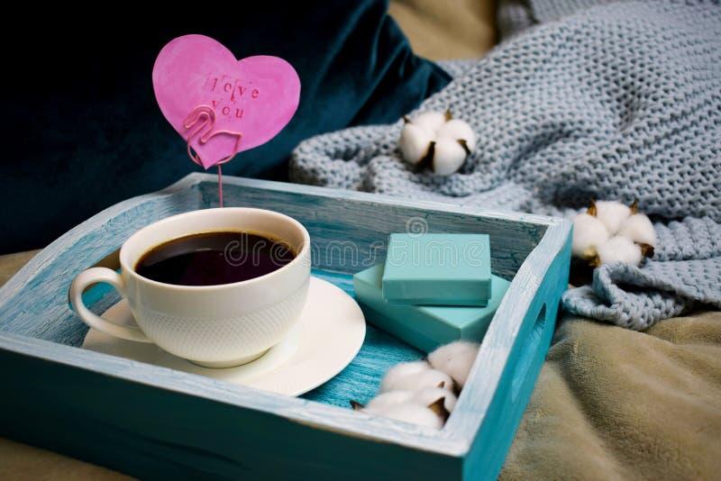 Mattina romantica sul San Valentino - prima colazione a letto su un vassoio di legno del turchese un la tazza di caffè, contenito immagini stock
