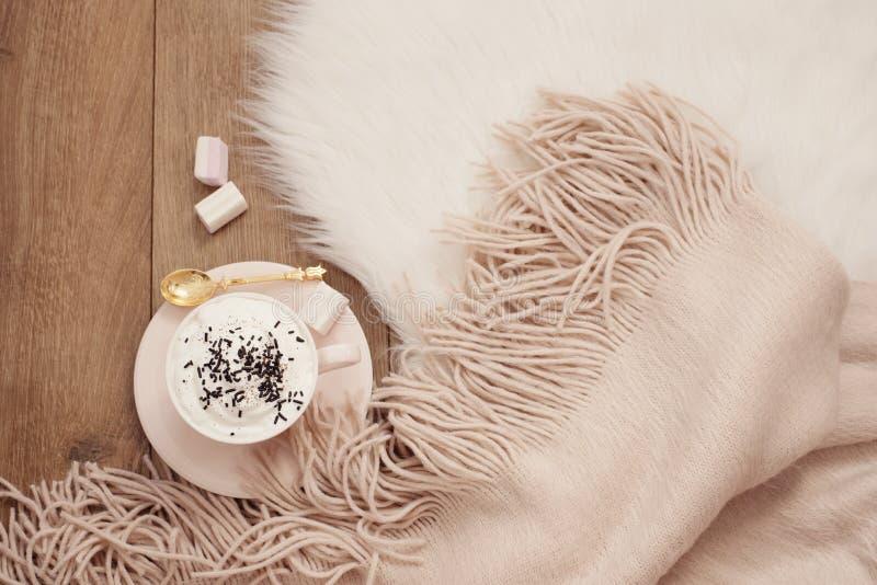 Mattine accoglienti di inverno Cappuccino e una sciarpa calda su un tappeto bianco della pelliccia sul pavimento immagini stock