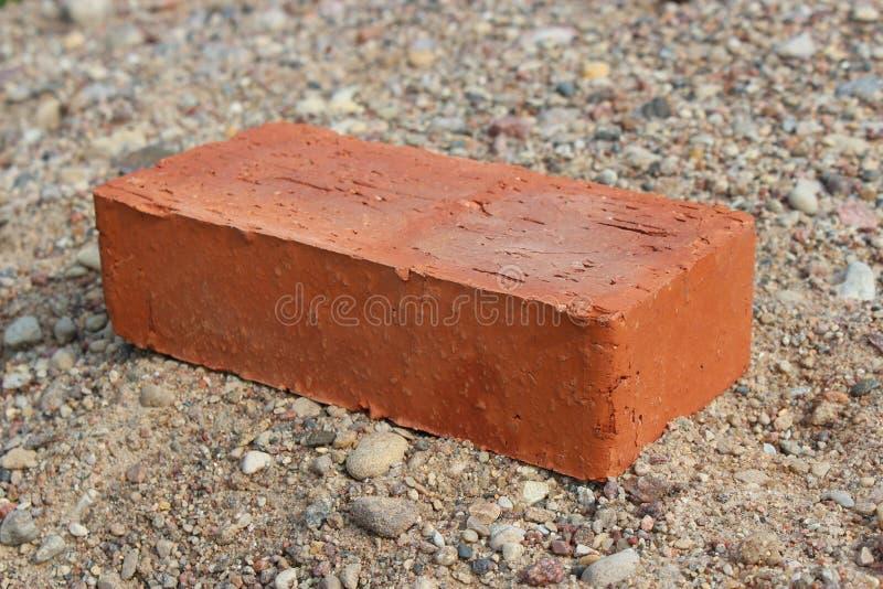 Mattone rosso che si trova sulla sabbia immagini stock libere da diritti