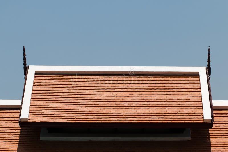 Mattonelle di tetto arancio con il fondo del cielo blu fotografia stock