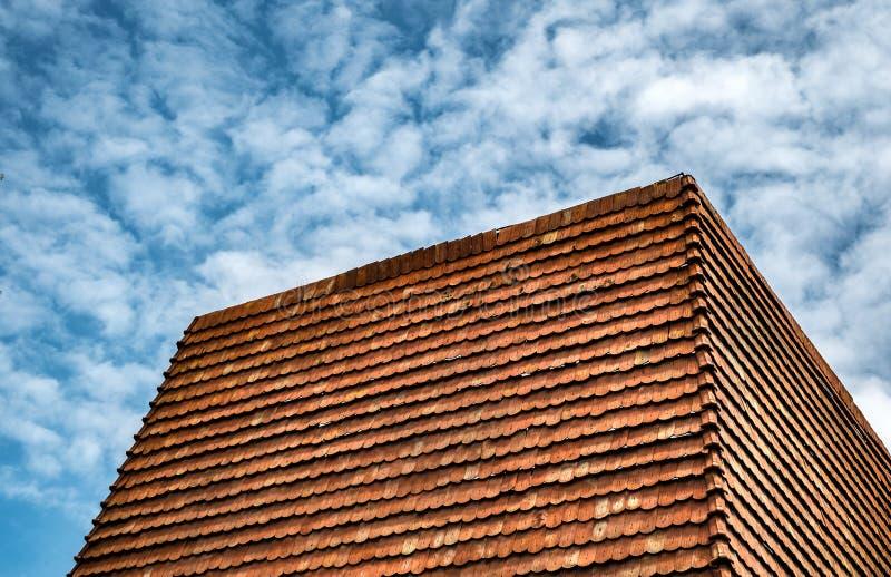 Mattonelle di tetto rosse sul cielo nuvoloso fotografia stock