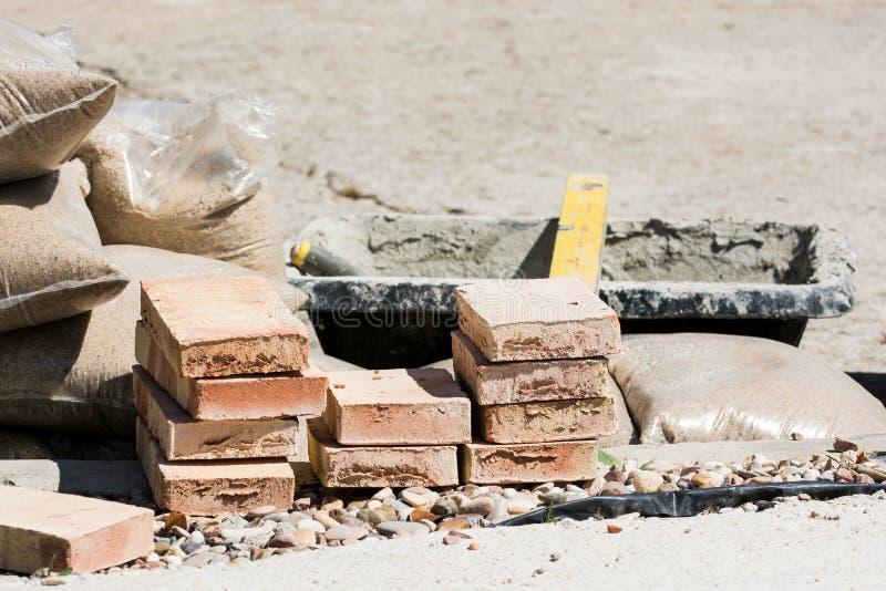 Mattoni, cemento, sabbia e materiali da costruzione fotografie stock