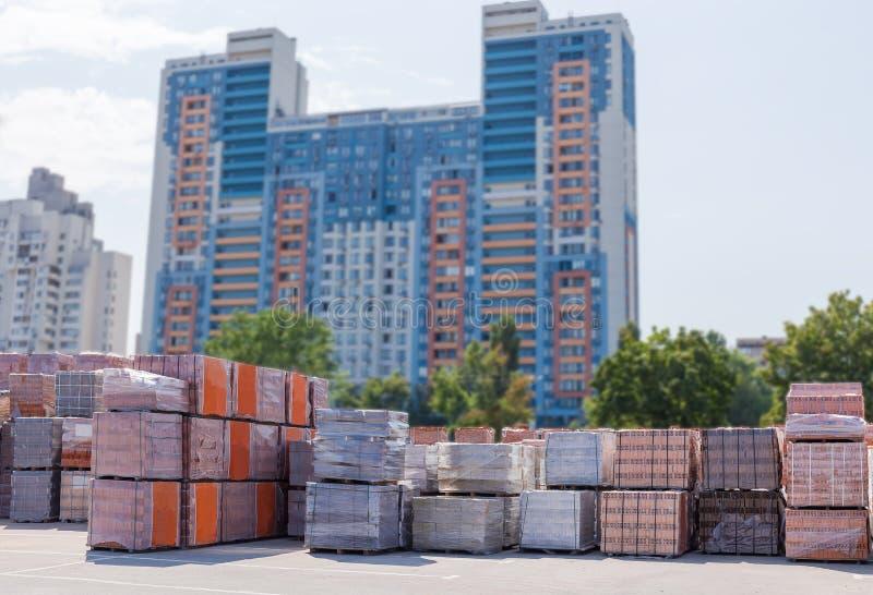 Mattoni di costruzione differenti sul magazzino all'aperto contro degli edifici residenziali immagini stock