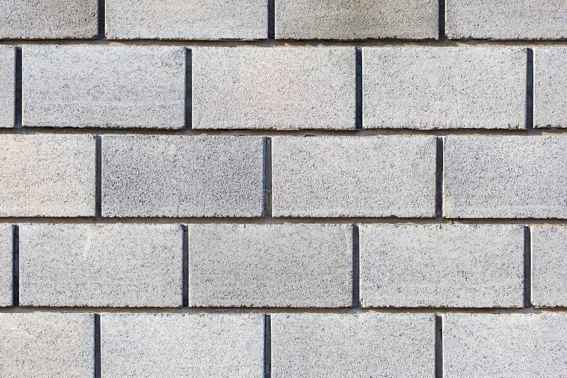 Mattoni grigi, parete fatta di grandi blocchi grigi Fondo grigio fotografia stock libera da diritti