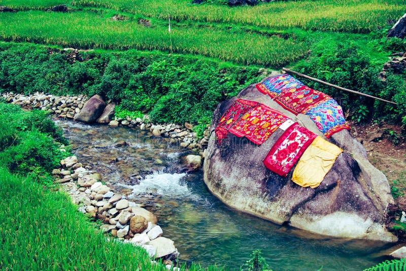 Mattor som torkar på ett stort, vaggar av en flod Handtvagning, traditionell metod arkivfoto