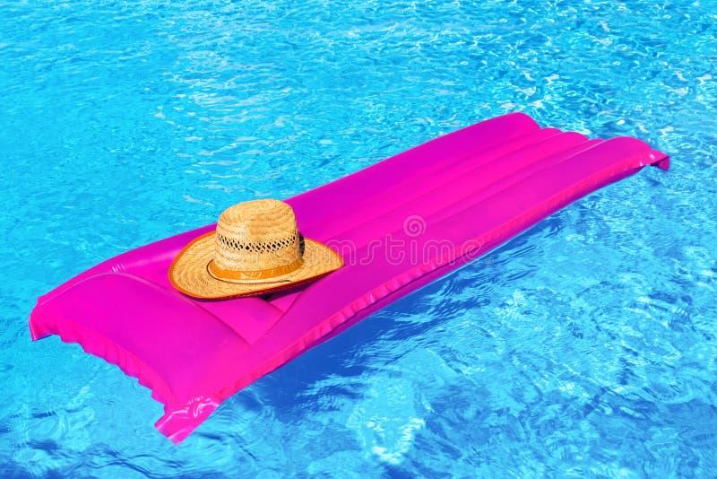 Mattrass roses d'air avec le chapeau dans la piscine photographie stock