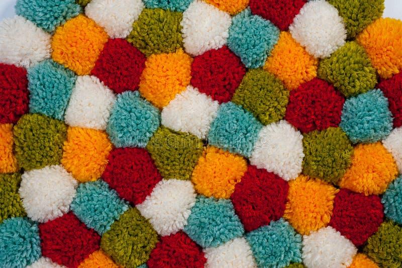 Mattt av pompons som göras från mång--färgat handgjort garn royaltyfri foto