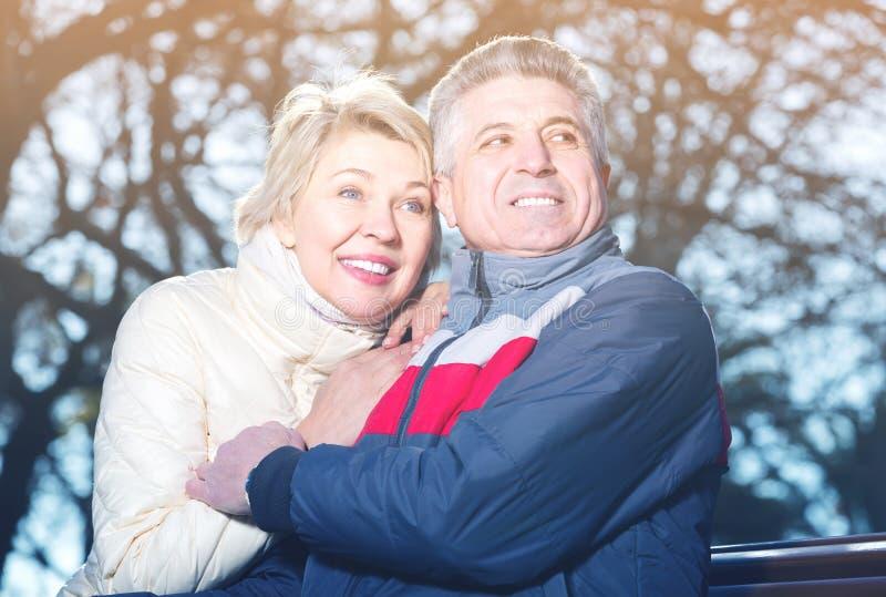 Mature поженилось пары сидя на скамейке в парке стоковая фотография rf